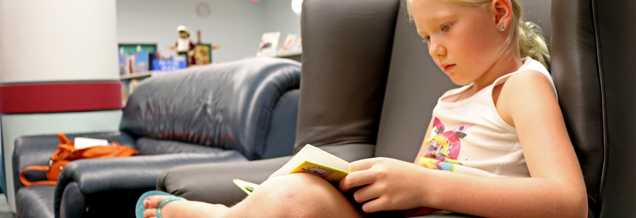 child reading book in chair