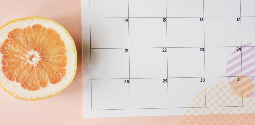 calendar on table with orange next to it
