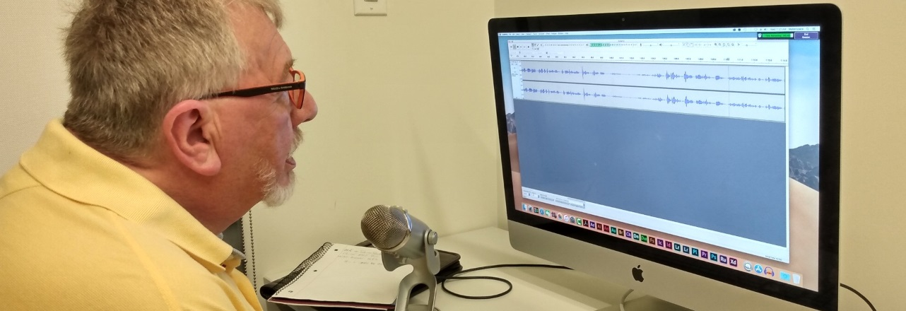 Man recording his voice on to a computer with a microphone
